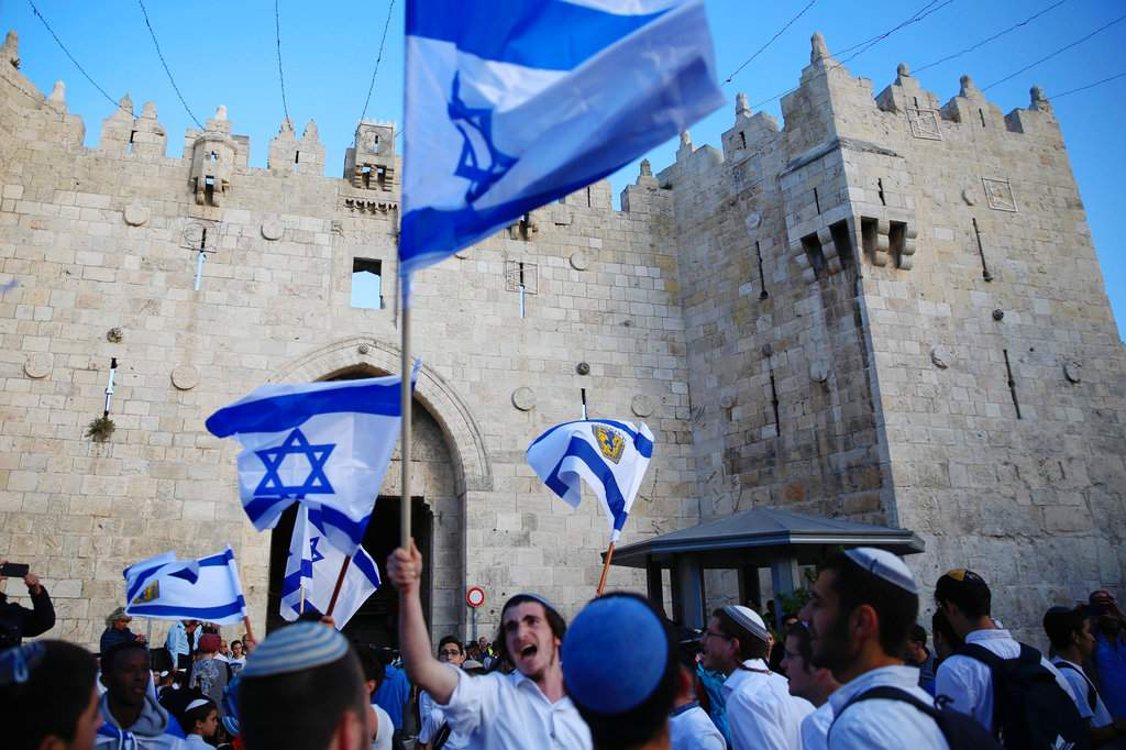 FILE - In this Sunday, May 13, 2018, file photo, Israelis wave national flags outside the Old City's Damascus Gate, in Jerusalem. Israel's parliament has approved a controversial piece of legislation that defines the country as the nation-state of the Jewish people. Opponents and rights groups have criticized the legislation, warning that it will sideline minorities such as the country's Arabs. (AP Photo/Ariel Schalit, File)